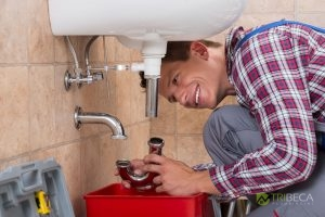 Man Working on Drain Pipe Under Sink