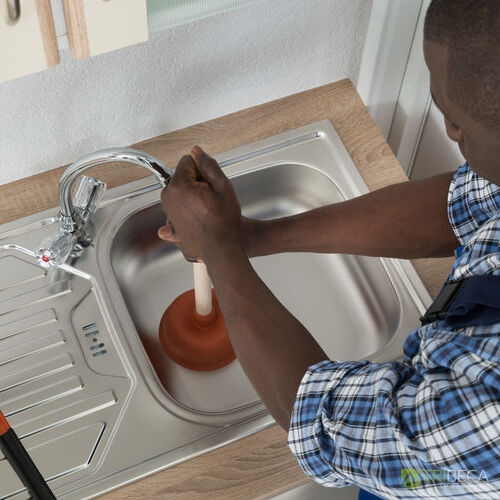 Close-up Of African Male Plumber Cleaning Sink With Plunger